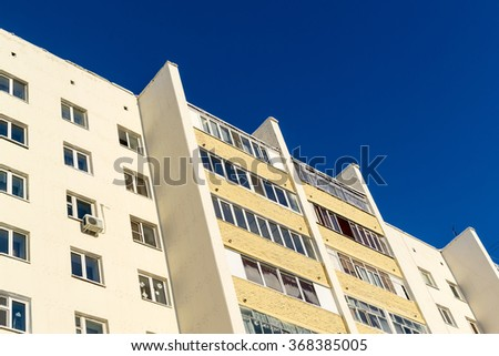 Architecture abstract of a white apartment building block set against a bright blue summer sky. Copy space area with nobody in the scene - stock photo