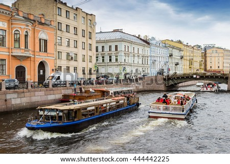 Architecture along water canal in Saint Petersburg, Russia. View of pleasure boats sailing on Moyka river.