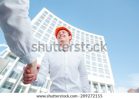 architecture and home renovation concept - builder shaking partner hand against new structure - stock photo