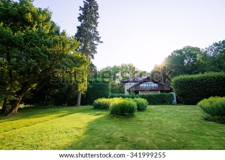 Architecture and nature. Beautiful wooden house with balcony in green summer park. - stock photo