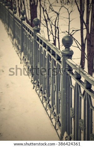 architecture and part of an old iron fence in vintage style of winter park in the photo from a retro effect