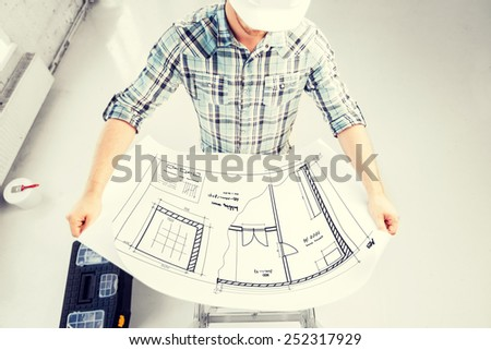 architecture and renovation concept - male architect in helmet with blueprint - stock photo