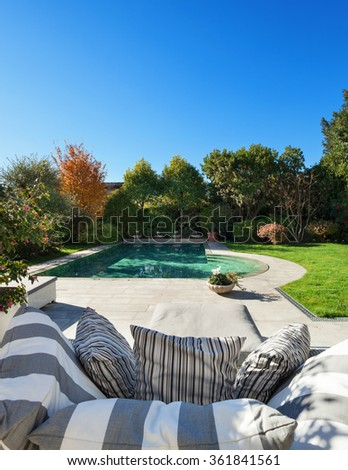 Architecture; beautiful garden with pool, view from the armchair - stock photo