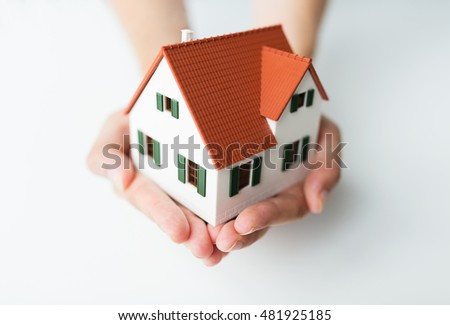 architecture, building, mortgage, real estate and people concept - close up of architect hands holding living house model