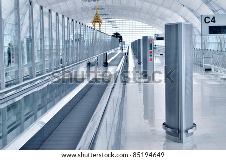 Architecture detail of a corridor with walkway inside departure terminal of Bangkok Airport in Thailand - stock photo