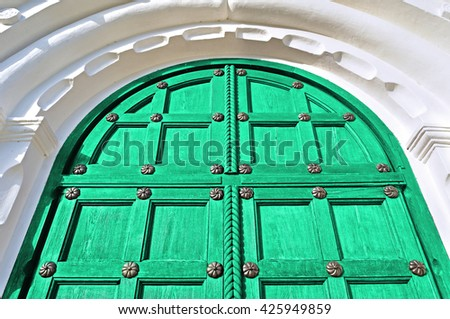 Architecture detailed background - aged wooden door of bright green color with metal rivets and upper arch of white stone - vintage architecture background - stock photo