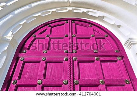 Architecture detailed background - aged wooden door of magenta color with metal rivets and upper arch of white stone - vintage architecture background - stock photo