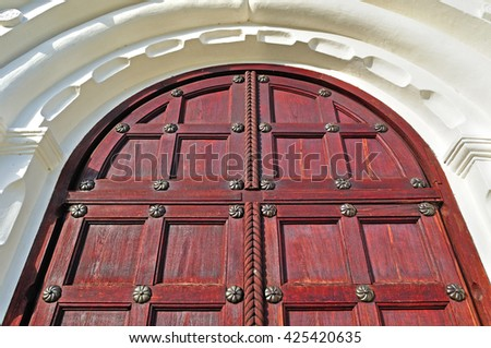 Architecture detailed background - aged wooden door of red color with metal rivets and upper arch of white stone - vintage architecture background - stock photo