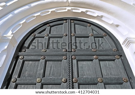 Architecture detailed background - aged wooden grey door with iron rivets and upper arch of white stone - vintage architecture background - stock photo