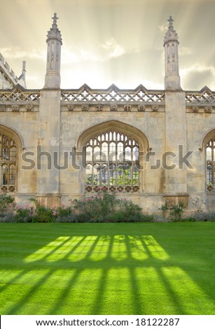 Architecture in Cambridge University, England. Kings College wall with window casting beautiful sunlight. - stock photo