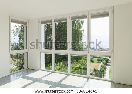 Architecture, interior of a modern house, wide room with windows - stock photo