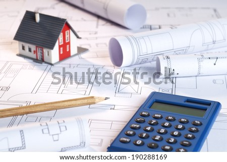 Architecture model with construction plans and calculator. - stock photo