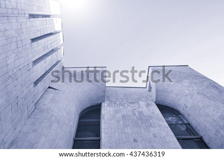 Architecture modern background - perspective bottom view of high building architecture details of concrete and glass. Cold urban tones tones applied. Architecture futuristic cityscape. - stock photo