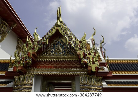 Architecture of  Wat Pho, Bangkok showing chofas (roof finials) and gilded hang hong (lower finial), all parts of the undulating, serpentine shaped lamyong (bargeboard). - stock photo