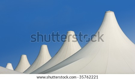architecture: white roofs of tents aligned over blue sky