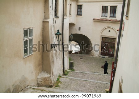 Archway at white tenement house at Prague's old town. - stock photo