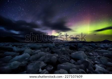 Arctic Magic Lights over the frozen fjord (Aurora Borealis) - stock photo