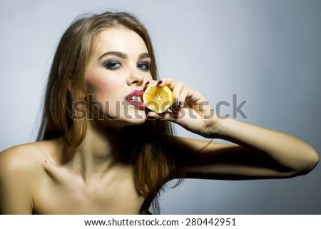 Ardent blonde girl portrait with bright make up looking forward holding half of fresh juicy orange standing on gray background copyspace, horizontal picture - stock photo