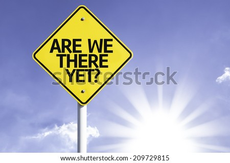 Are We There Yet? road sign with sun background  - stock photo