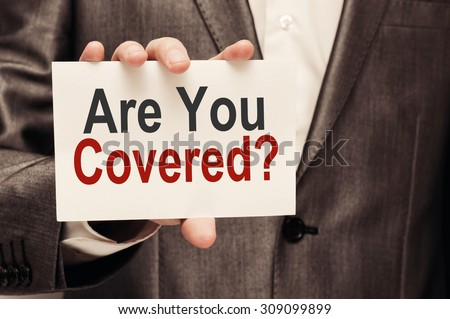 Are you Covered? Man holding a card with a message text written  - stock photo