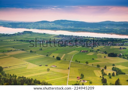 Areal photograph of read crossing, green fields stripes, trees and houses near Neuschwanstein castle in Germany - stock photo