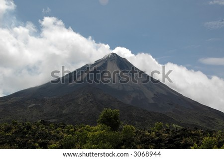 Arenal volcano against a blue sky with white clouds, Costa Rica