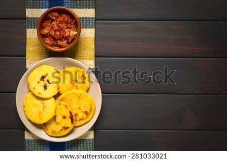 Arepas, fried cornmeal patties, with Colombian hogao sauce (tomato and onion cooked). Arepas are traditionally eaten in Colombia and Venezuela. Photographed on dark wood with natural light. - stock photo