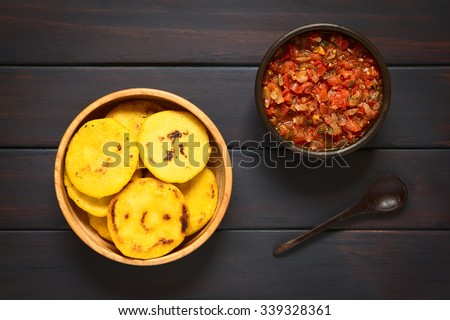 Arepas or corn meal patties with Colombian hogao sauce (tomato and onion cooked), arepas are traditionally eaten in Colombia and Venezuela. Photographed on dark wood with natural light.