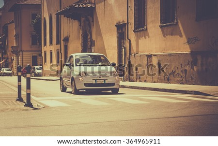 AREZZO, ITALY - JUNE 26, 2015: The newest version of Fiat 500, one of the most popular small city cars in Italy, on cross roads in tuscan Arezzo city, Italy - stock photo