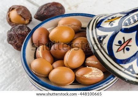 Argan Fruit on a wooden tabletop in a Moroccan Tajine - stock photo