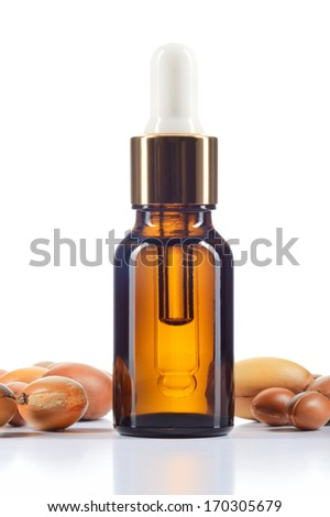 Argan oil and argan nuts isolated on white background. Body oil in brown bottle. - stock photo