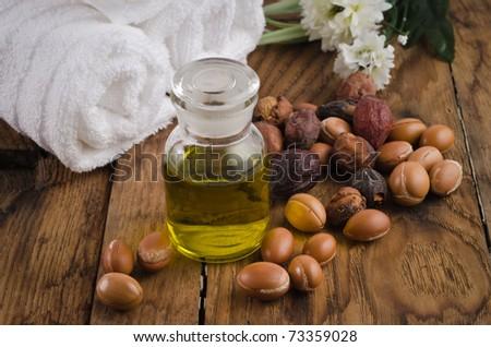 Argan oil for massage and argan fruit. Spa mood - stock photo