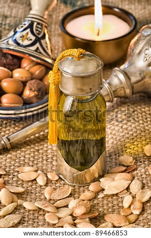Argan oil in a glass bottle with fruits and Moroccan objects on the background - stock photo