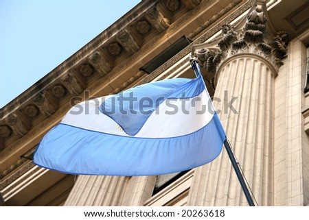 Argentina flag waving in the wind with old building in background. - stock photo