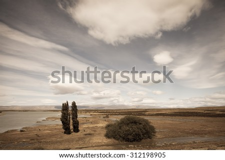 Argentine Patagonia on a windy day. Yellow flat desert with shallow lakes - stock photo