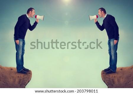 argument conflict men shouting megaphones over canyon - stock photo