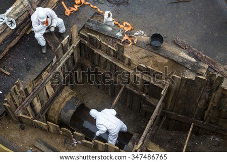Ariar view of city service does emergency repair work on damaged pipe at center of a city - stock photo