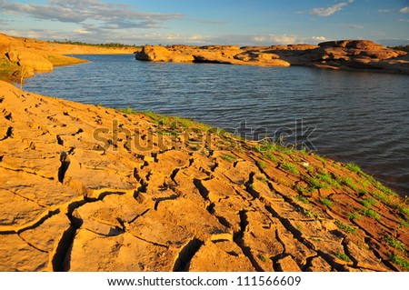 Arid land and lake - stock photo
