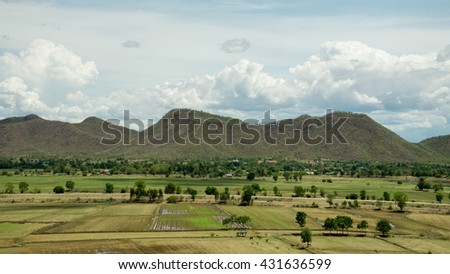 Arid lands have many cow , bright sky,long mountain, cloud ,Rice Fields, Kanchanaburi Province, Thailand - stock photo