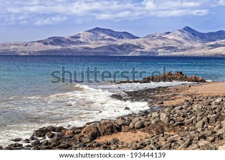 Arid landscape in the sea shore in Lanzarote with volcanoes on the background. - stock photo