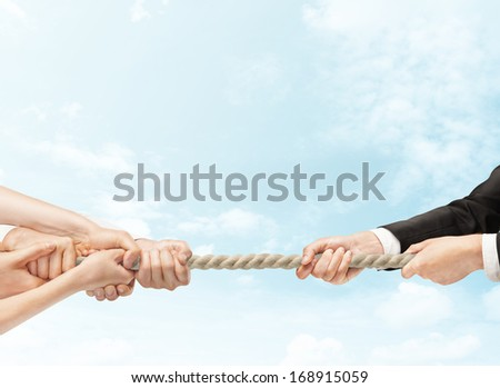 arious hands during tug war on sky backgrounds - stock photo