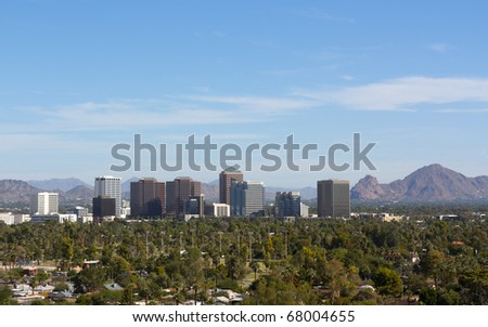 Arizona capital city of Phoenix uptown against east valley mountains - stock photo
