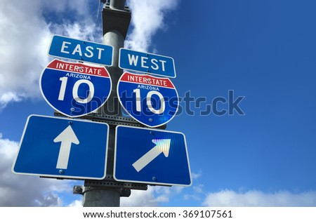 Arizona I10 East West Highway direction signs with copy space to right on blue sky - stock photo
