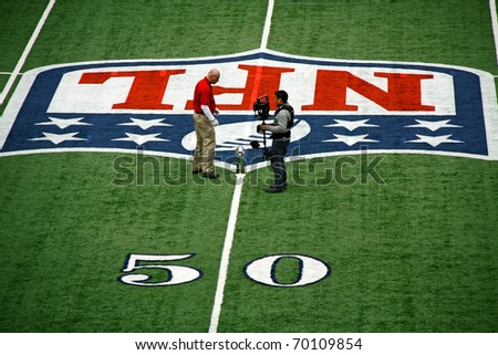 ARLINGTON - JAN 26: In preparation for Super Bowl XLV an unidentified cameraman and worker discuss placement of the trophy in Cowboys Stadium in Arlington, TX. Taken January 26, 2011 in Arlington, TX. - stock photo