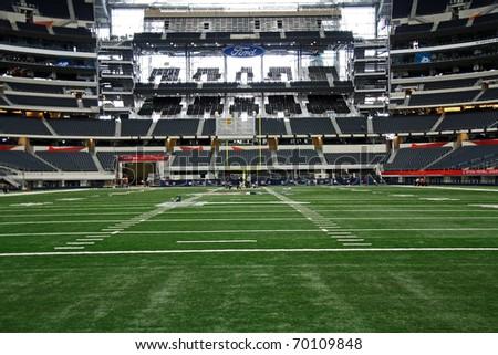 ARLINGTON - JAN 26: Unidentified workers prepare the field for the Packers Steelers Super Bowl XLV in Cowboys Stadium in Arlington, Texas. Taken January 26, 2011 in Arlington, TX. - stock photo