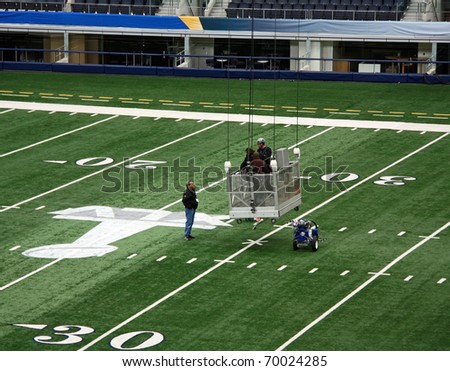 ARLINGTON - JAN 26: Unidentified workers prepare the field in Cowboys Stadium in Arlington, Texas for Super Bowl XLV. Taken January 26, 2011 in Arlington, TX. - stock photo