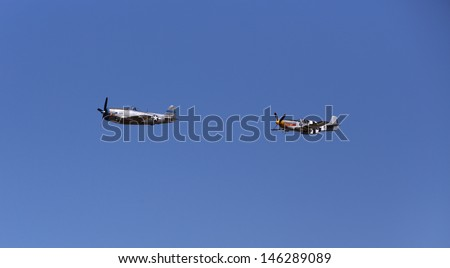 ARLINGTON -  JULY 13: A restored World War II P-47 D and a  P-51 B 10NA Mustang was seeing flying in formation over Arlington Air Field on 13 July 2013  near Seattle, WA. - stock photo