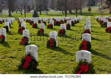 ARLINGTON, VA - DECEMBER 18: Christmas wreaths on gravestones in Arlington National Cemetery on December 18, 2011. The wreathes have been donated each year since 1992. - stock photo