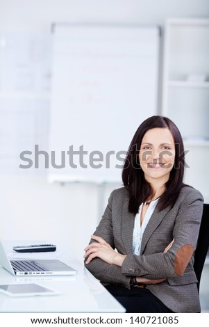 Arm crossed businesswoman sitting in front of her laptop