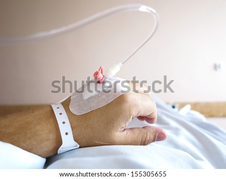 Arm of a male patient in the hospital with an iv intravenous drip - stock photo